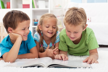 telling: Three kids having fun reading a book laying on the floor