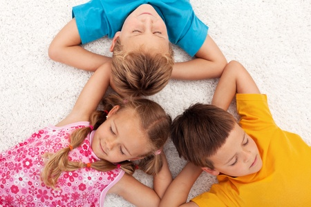 Kids taking a break relaxing on the floor with eyes closed photo