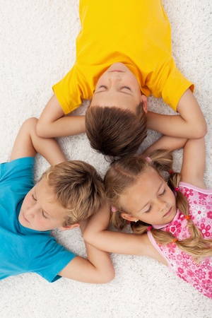Three kids relaxing and meditating on the floor photo