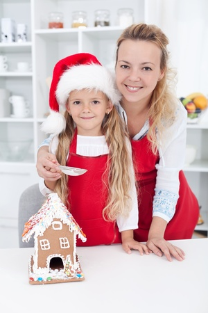 Woman and little girl making a gingerbread cookie house at christmas photo