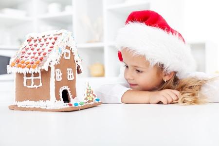 weihnachtskuchen: Mein Weihnachten Lebkuchen Haus - kleines M�dchen in Ehrfurcht vor ihrer eigenen Arbeit