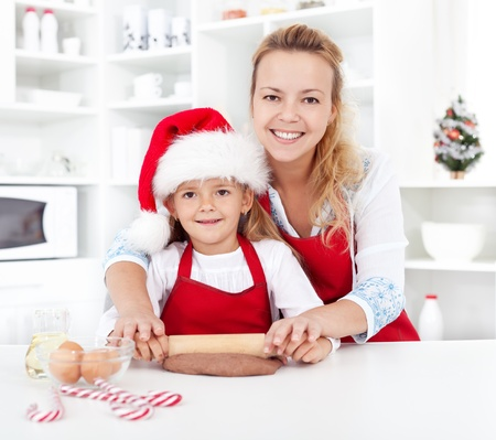 Woman and little girl stretching the christmas gingerbread cookies dough photo