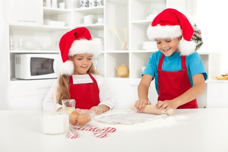 Happy kids with santa hats making christmas cookies photo