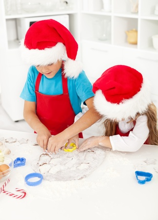 Kids making christmas cookies cutting the dough photo
