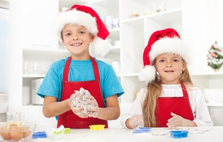 Kids making christmas cookies wearing santa hats and aprons photo