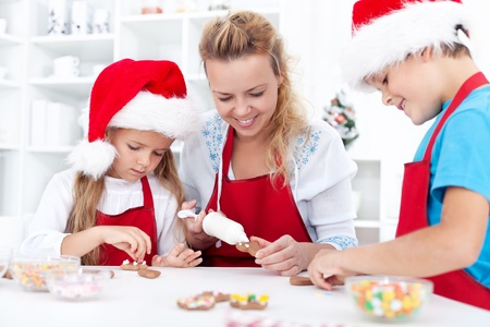 Family decorating christmas cookies together in the kitchen photo