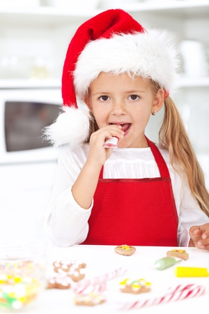 Little girl decorating christmas cookies tasting the icing photo