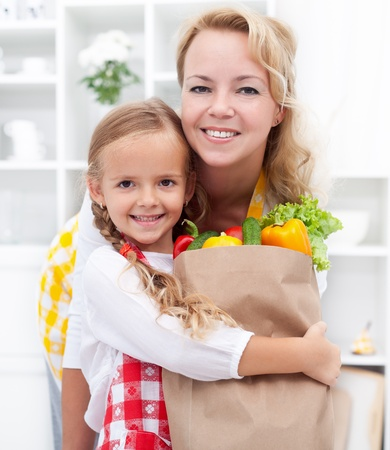 Happy little girl and woman with the groceries bag wearing aprons photo