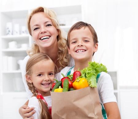 ni�os de compras: Familia feliz con la bolsa de supermercado llena de verduras frescas - concepto de vida sana