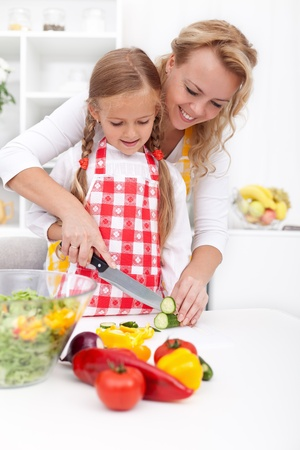 Happy woman and child preparing healthy food together photo