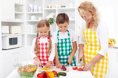 people helping people: Happy family with aprons preparing healthy fresh salad together
