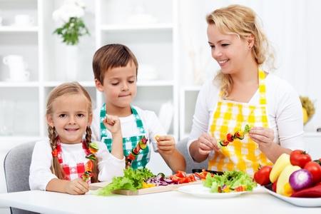 delantal: Familia de preparar una comida verduras frescas juntos en la cocina