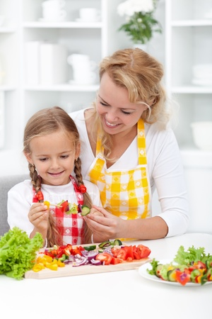 Happy mother and child preparing healthy fresh food photo