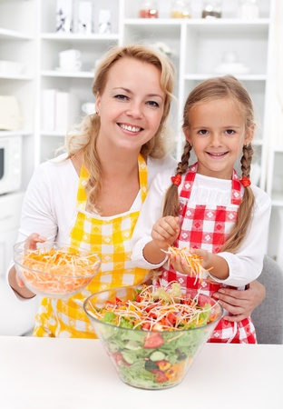 Woman and little girl preparing a healthy salad in a big bowl photo