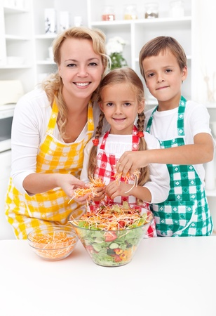 Happy healthy family preparing a bowl of fresh salad together in the kitchen photo
