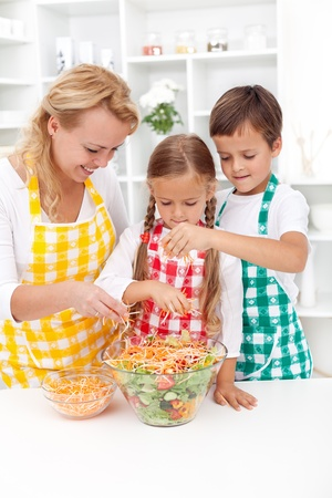 The last touch on a fresh salad - family preparing healthy food photo