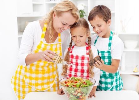 aceite de cocina: Familia en la cocina condimento de la ensalada verduras frescas Foto de archivo