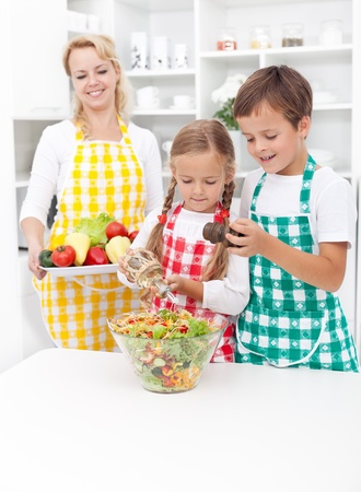Kids preparing and seasoning a healthy fresh salad in the kitchen photo