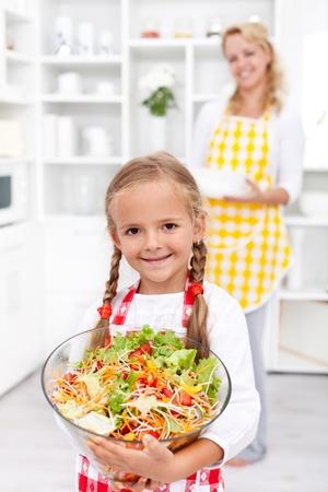 comidas saludables: Feliz ni�a saludable, con un taz�n grande de ensalada de verduras frescas en la cocina Foto de archivo