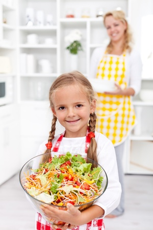 preparations: Happy healthy girl with large bowl of fresh vegetables salad in the kitchen
