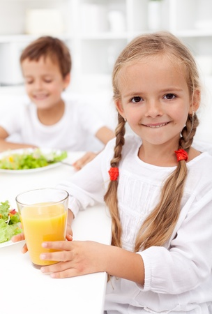 hungry children: Happy healthy kids eating fresh food - closeup Stock Photo