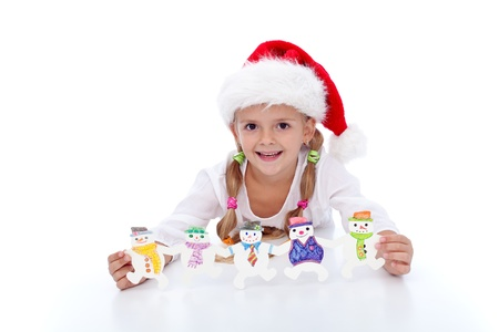 Happy girl at christmas time with handmade decoration and santa hat photo