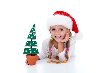 Happy girl with christmas tree decoration and santa hat photo