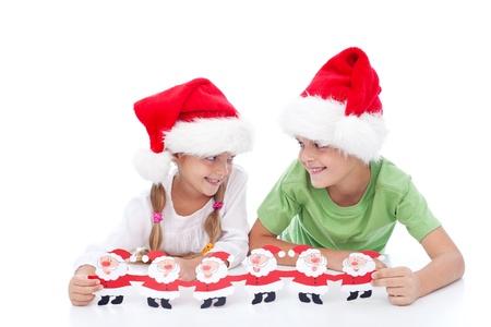 Mischievous christmas kids waiting for santa holding paper decoration photo