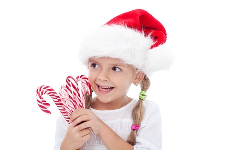Little laughing girl with santa hat and candy canes around christmas time - isolated photo