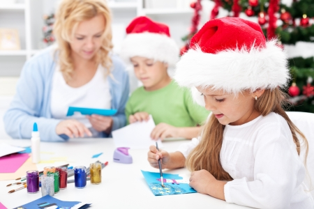 Family making seasonal greeting cards together at christmas time photo