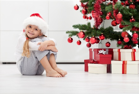 I have lots of presents - smiling little girl in front of the christmas tree photo