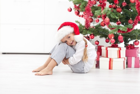 Happy Little Girl Sitting Under The Christmas Tree With Presents Stock Photo