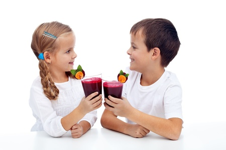 clinking: Ni�os tintineando con zumo de remolacha y zanahoria - dieta saludable Foto de archivo