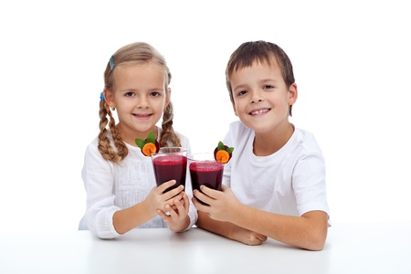 Cheers - healthy kids clink glasses of fresh beetroot and carrot juice photo