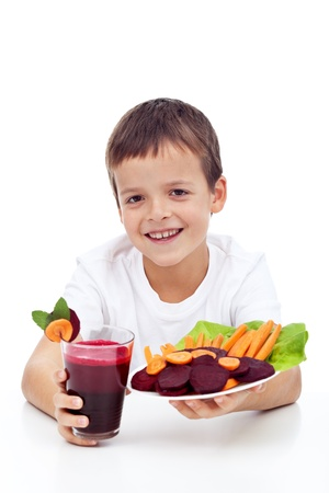 Happy child with fresh betroot juice and vegetable slices - healthy eating concept photo