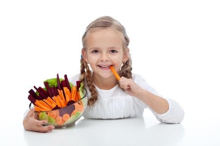 munching: Little girl munching on a carrot stick holding bowl of vegetables