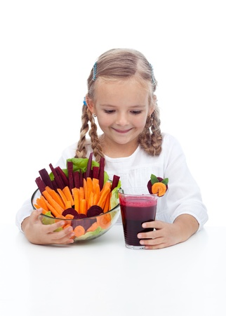Little girl with healthy vegetables and freshly squeezed juice photo