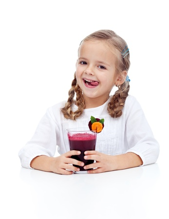 Fresh and healthy beetroot juice in happy little girl hands photo