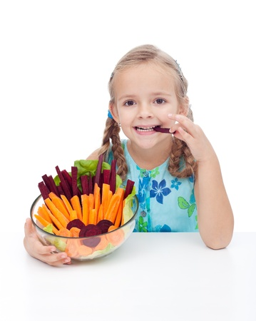 munching: Little girl holding bowl of vegetables and munching betroot and carrot