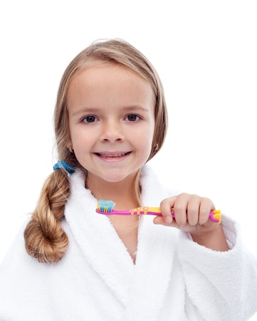 Little girl washing teeth after bath - personal hygiene education photo