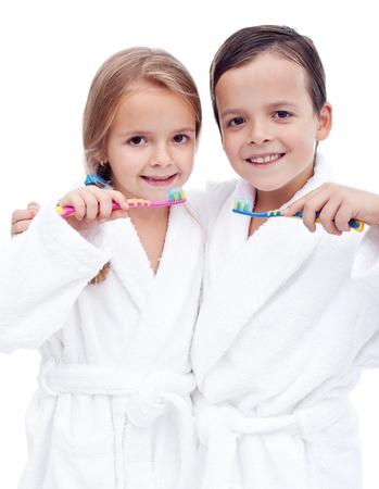 higiene bucal: Hermosos hijos preparando para cepillarse los dientes usando batas blancas - aislado, primer plano