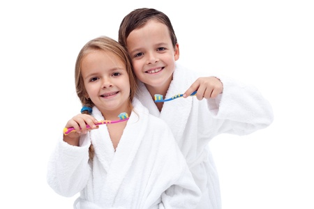 Happy and clean kids washing teeth wearing batrobes - isolated photo