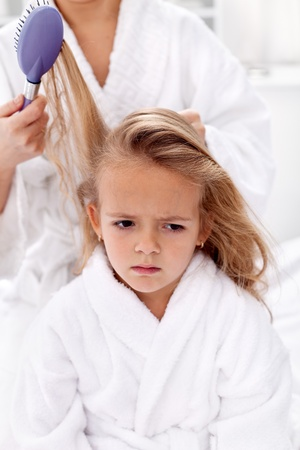 little girl bath: The price of  beauty is pain - little girl sulking while combing Stock Photo