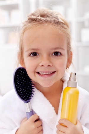 hair conditioner: Happy little girl after bath with hairbrush and sprayer