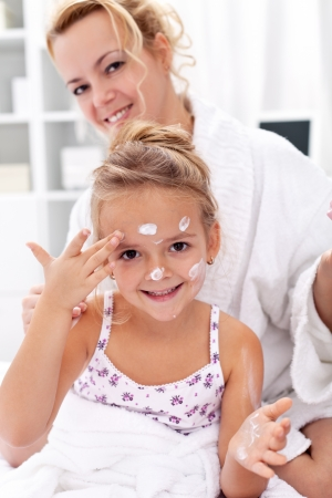 After bath body care with happy woman and little girl photo