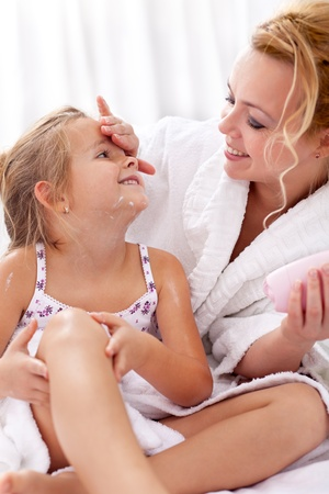woman face cream: Applying face cream and body lotion - woman and little girl after bath