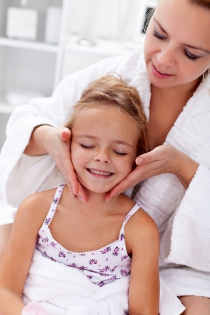 moisturizing: Applying face cream after bath - little girl and woman having fun Stock Photo