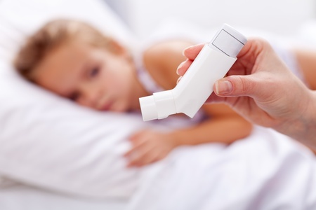 inhalation: Sick kid with inhaler in foreground - asthma or other respiratory illness