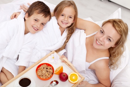 Breakfast in bed for mom-kids pampering their mother photo
