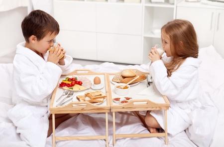 Ontbijt op bed - kinderen met een maaltijd in de ochtend Stockfoto